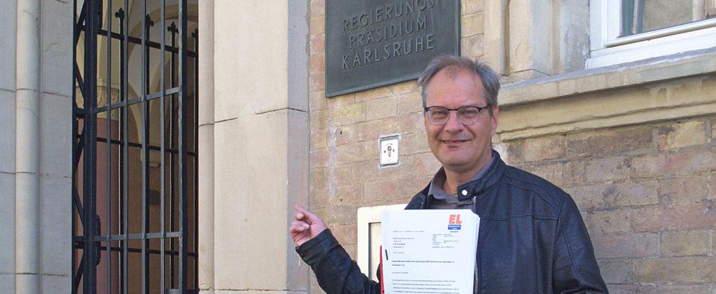 Bernd Binsch mit den gesammelten Unterschriften vor dem Regierungspräsidium Karlsruhe.
